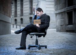 Business Man sitting on Office Chair on Street in stress asking for help